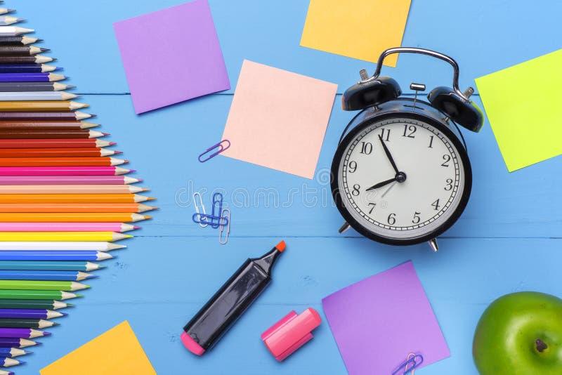 Träskrivbord med brevpapper och tomt klistermärkear, ringklocka och äpple Begreppsmässig bakgrund i stilen av tillbaka till arkivfoto