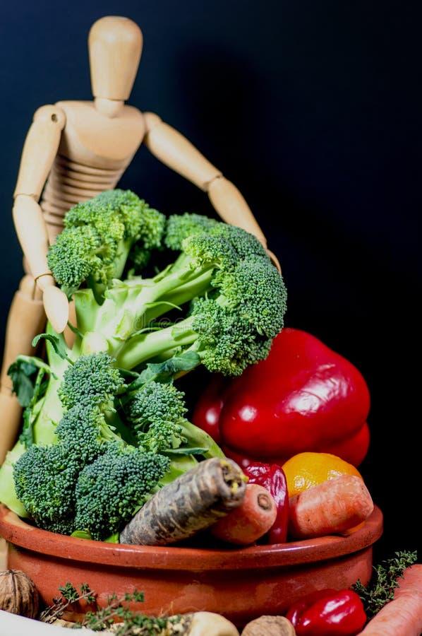 Träskyltdocka och en blandning av grönsaker arkivbild