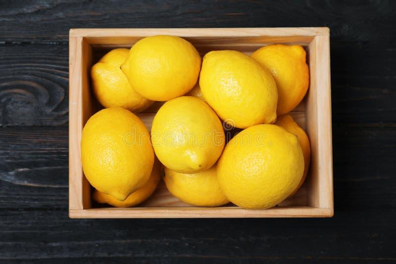 Träspjällåda mycket av nya citroner på mörk bakgrund arkivbilder