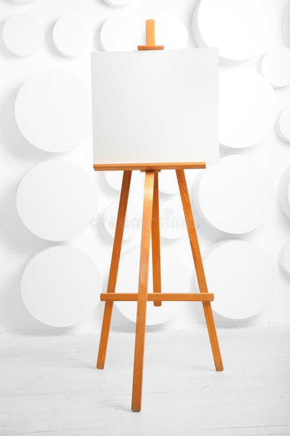 Trästaffli med tom kanfas i studion arkivfoto