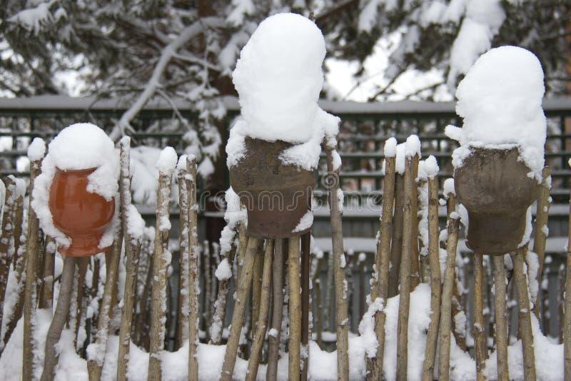 Trästaket och keramiska krus som täckas med snö arkivbilder