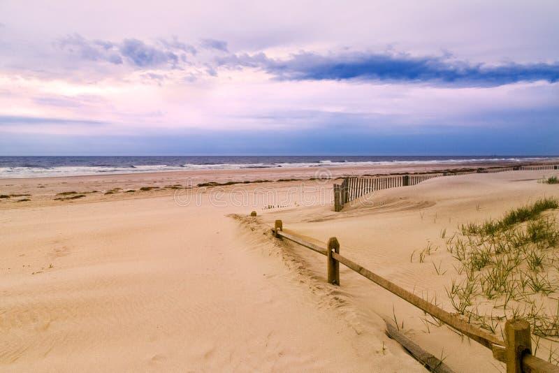 Trästaket och sandig strand fotografering för bildbyråer