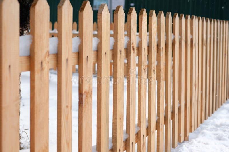 Trästaket som täckas med snö runt om trädgård i vintertid royaltyfria bilder