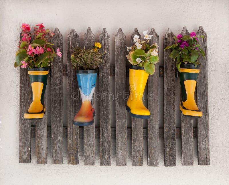 Trästaketdecoratet med blommor som planteras i gummistöveler royaltyfri fotografi
