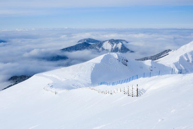 Trästaketet och skidar slingan i de Kaukasus bergen som täckas med snö royaltyfria bilder