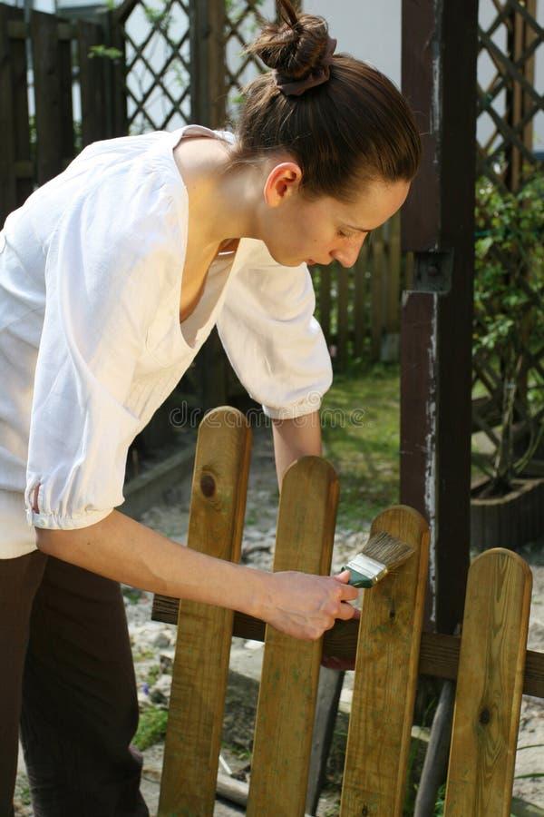 trästaketmålningskvinna arkivbild