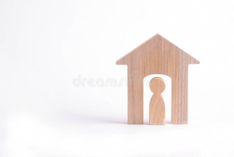 Trästatyett av en man i ett hus på en vit bakgrund Begreppet av ett lägenhethus, fastighet köpande sälja royaltyfri fotografi