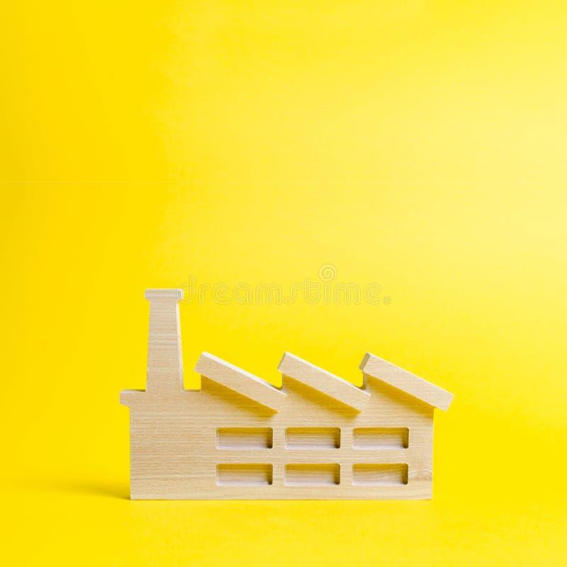 Trästatyett av en växt eller en fabrik på en gul bakgrund Återvinningråvaror Begreppet av bransch och produktion arkivfoto