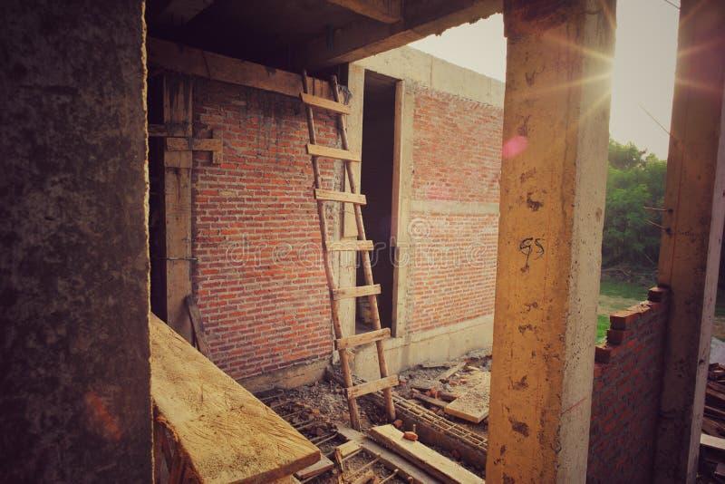 Trästegen lutar mot tegelstenväggen på constructioonplatsen royaltyfria bilder