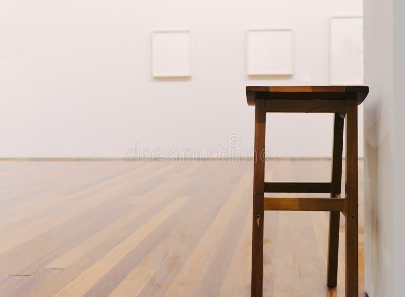 Trästol i det tomma museet som ser rum med målningar på väggen fotografering för bildbyråer