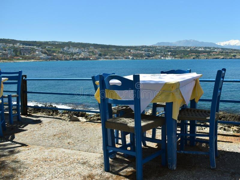 Trästolar och tabell i en krog på bakgrunden av havet arkivfoto