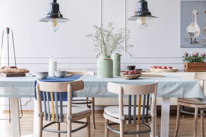 Trästolar på tabellen med blommor och mat i den vita stugamatsalinre med lampor och affischen Verkligt foto royaltyfria foton