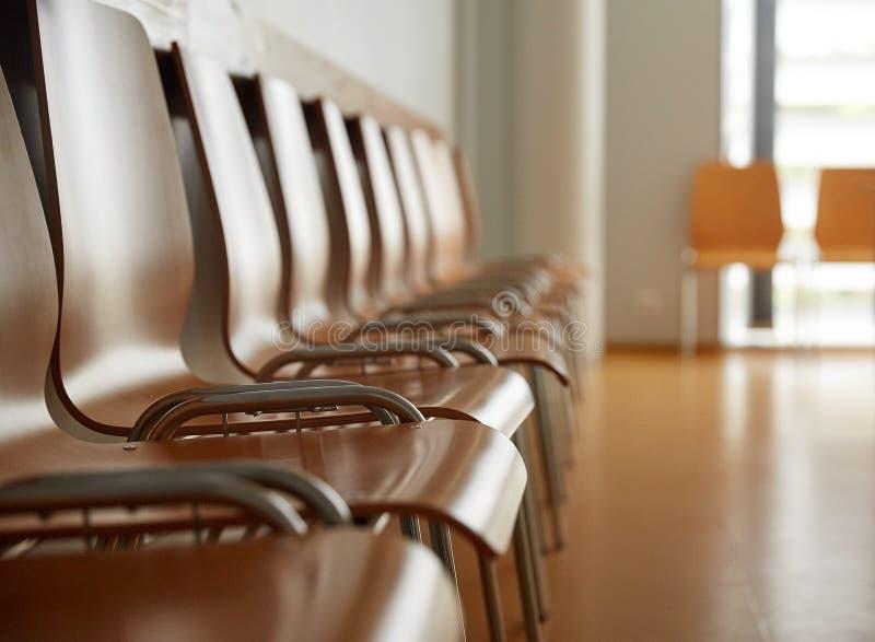 Trästolar på väntande rum för sjukhus arkivbild
