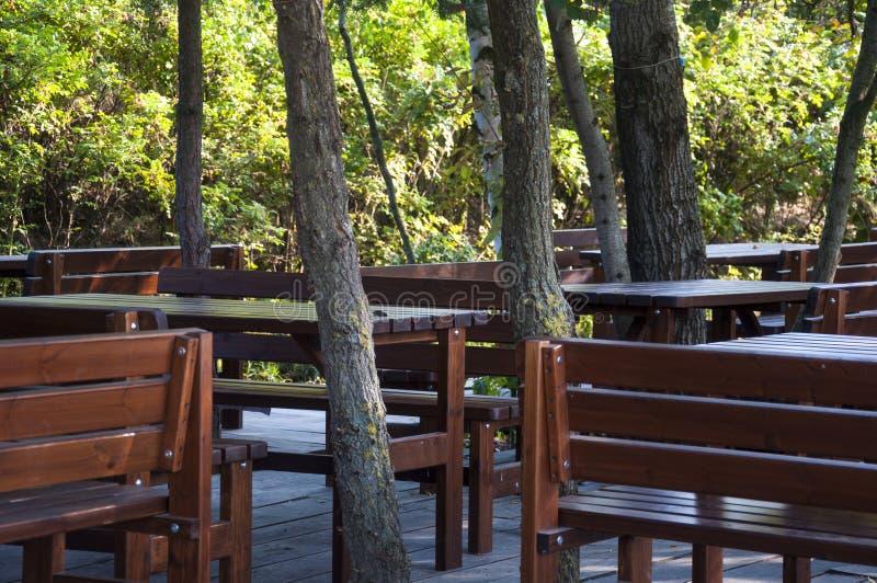 Trästolar tabeller i restaurangträdgård arkivbilder