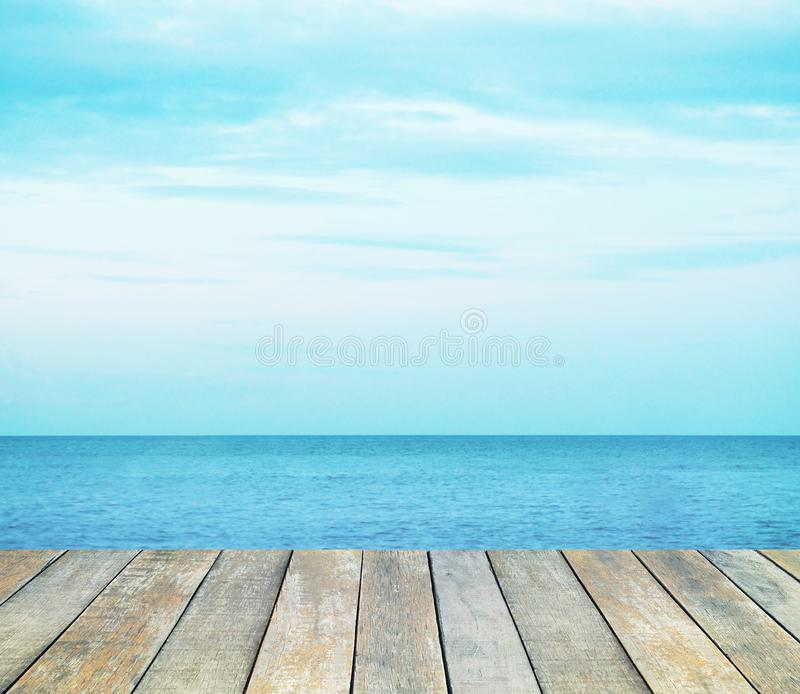 Trätabellöverkant över sommarhavet och blå himmel med vit molnbakgrund arkivfoton