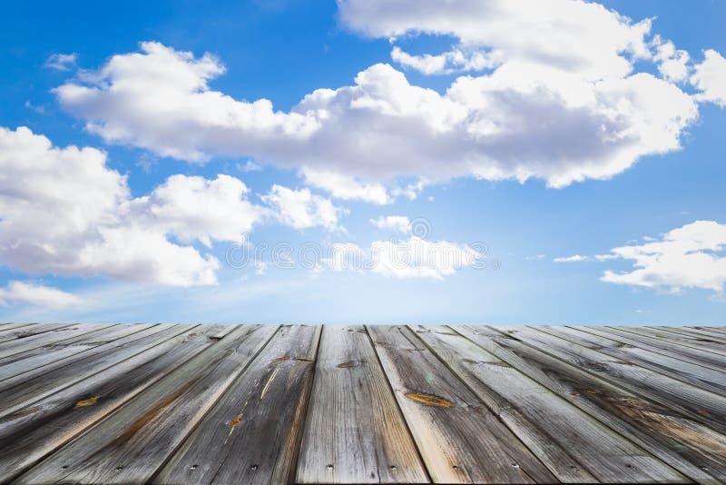 Trätabellöverkanten med blå himmel och vit fördunklar Utrymme för gåva en produkt arkivbild
