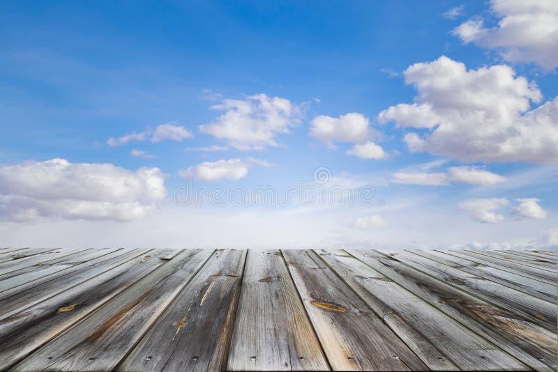 Trätabellöverkanten med blå himmel och vit fördunklar Utrymme för gåva en produkt arkivfoton