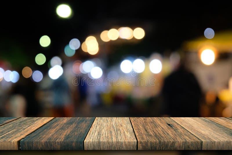 Trätabell för gammal tappning på framdel med den färgrika suddiga natten royaltyfri fotografi