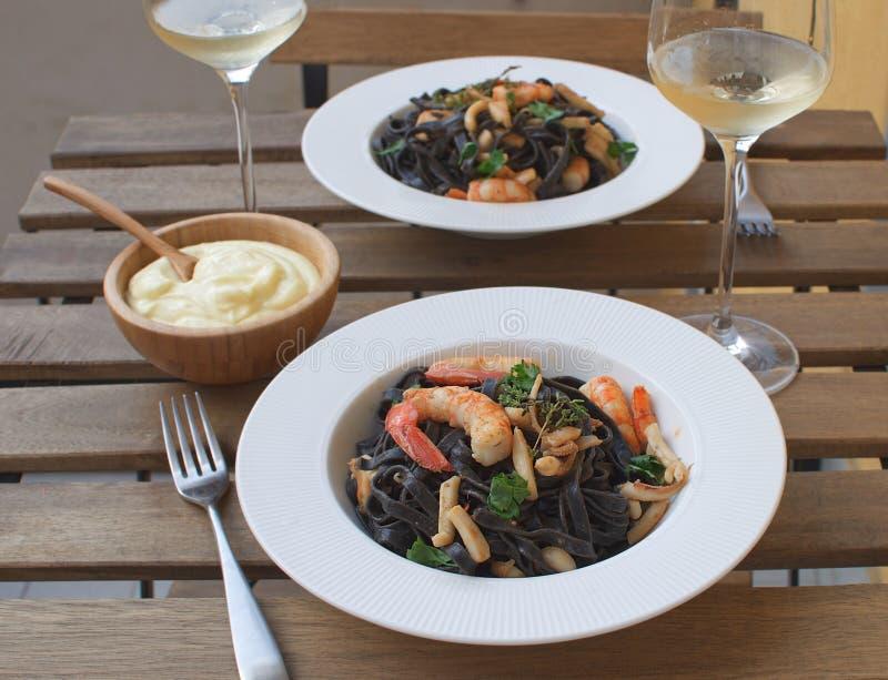 Trätabell för havs- för Alioli för vitt vin för räka för closeup för tioarmad bläckfiskfärgpulverpasta terrass restaurang royaltyfri bild