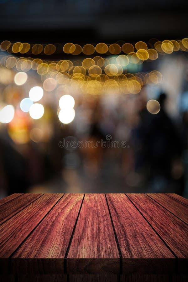 Trätabell framme av abstrakt suddig bakgrund arkivbild