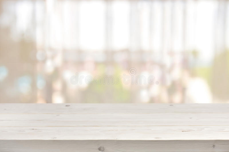 Trätabell framme av suddig genomskinlig bakgrund för fönstergardin royaltyfri bild