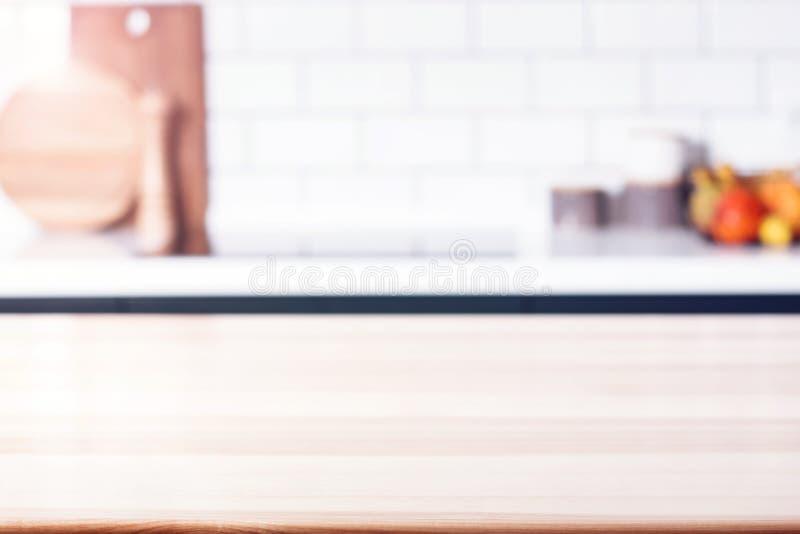 Trätabell framme av suddigt modernt kök royaltyfria bilder