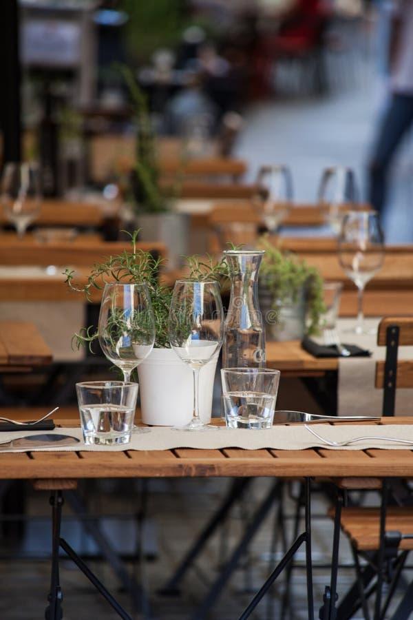 Trätabell i restaurangen som är utomhus- med vinexponeringsglas och vatten royaltyfria foton