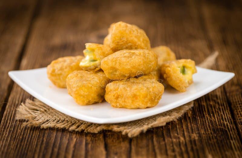 Trätabell med Chili Cheese Nuggets den selektiva fokusen arkivfoto