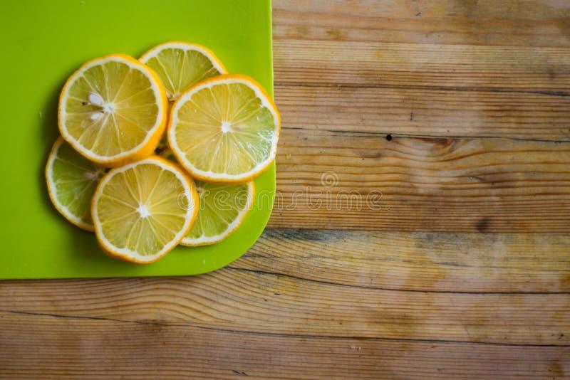 Trätabell med citronskivor på en skärbräda royaltyfria bilder