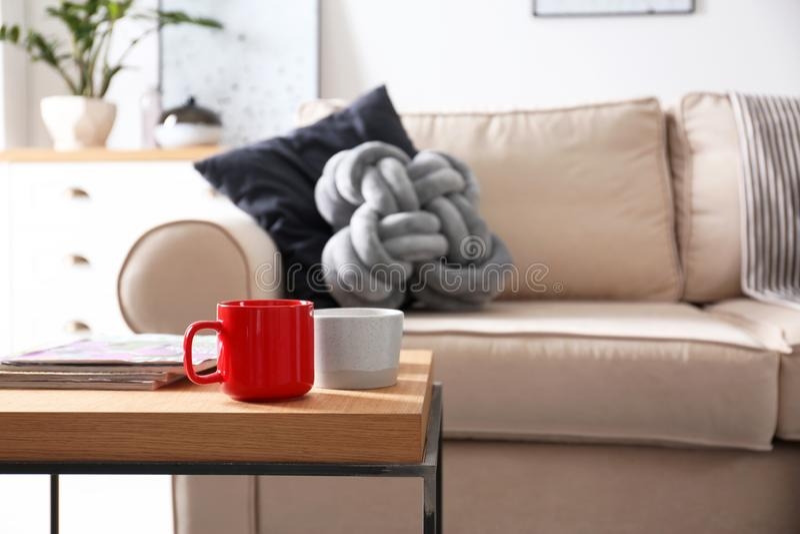 Tr?tabell med koppar och tidskrifter n?ra den bekv?ma soffan i vardagsruminre arkivbild