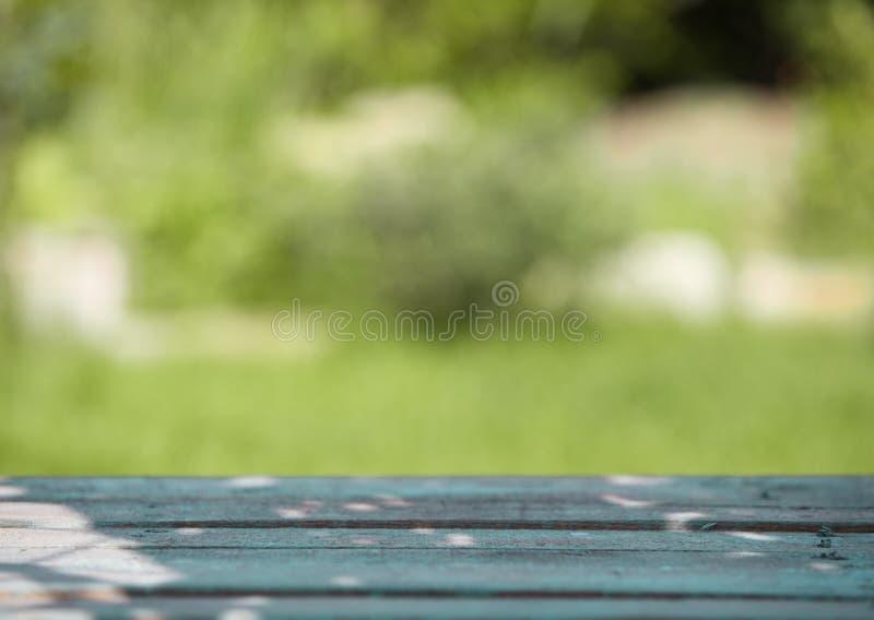 Trätabell mot en suddig grön bakgrund arkivfoto