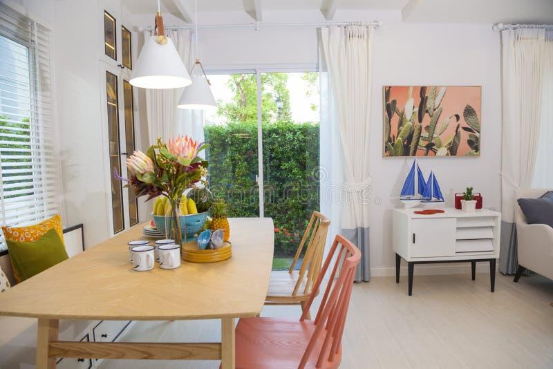Trätabell och rosa stol i dinning rum hemma Färgrik inre av dinning rum arkivfoton
