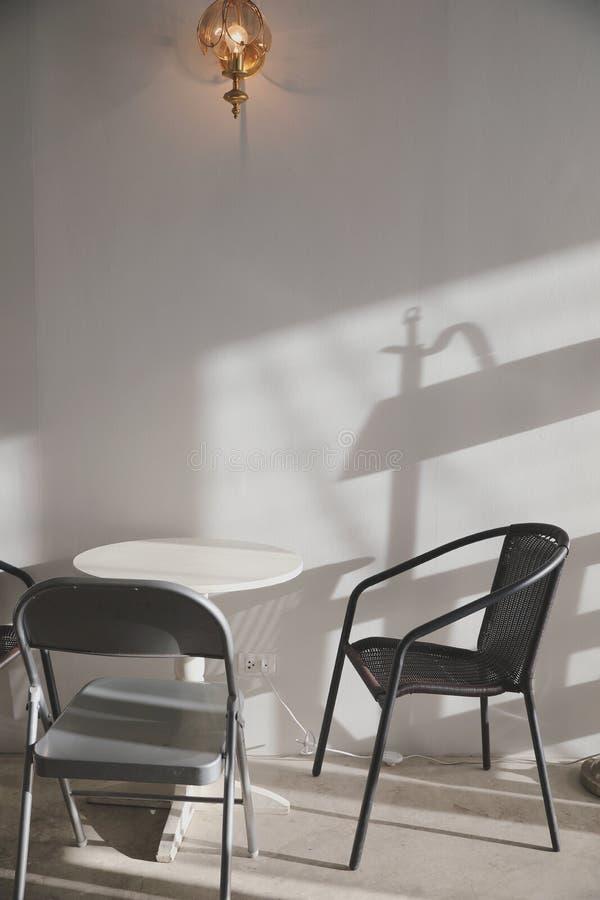 Trätabell och stolar med lampan på väggen royaltyfria bilder