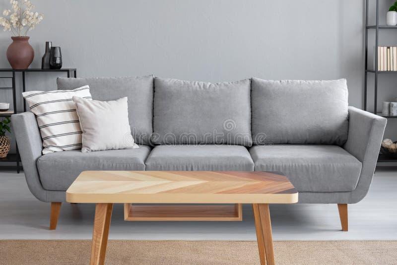 Trätabell och stor grå soffa med kuddar i vardagsrum av den moderiktiga lägenheten, verkligt foto royaltyfri fotografi