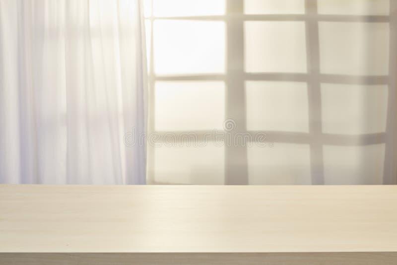 Trätabell på defocuced fönster med gardinen arkivfoton