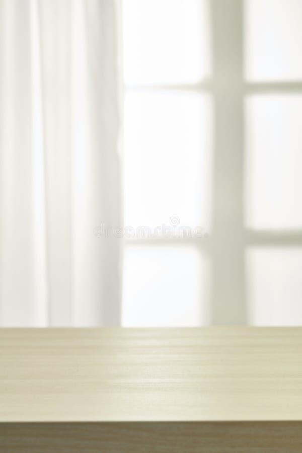Trätabell på defocuced fönster med gardinen fotografering för bildbyråer