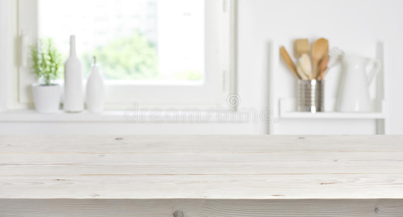 Trätabell på suddig bakgrund av kökfönstret och hyllor arkivbilder