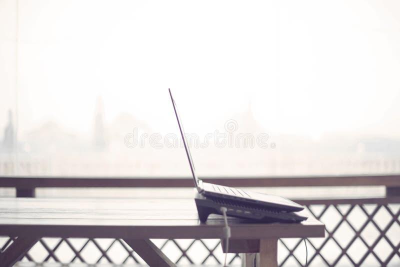 Trätabell på utrymmet för kopia för grej för internet för verandakontorsbärbar dator det moderna arkivfoto