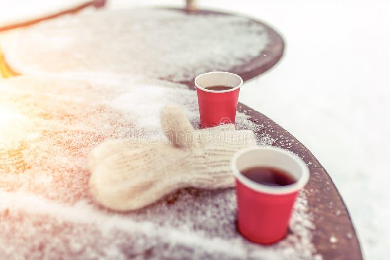 Trätabell som täckas med insnöad vinter i staden Två koppar kaffe och te Varma tumvanten på kuggen fritt avstånd royaltyfri foto