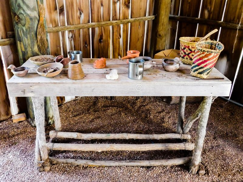 Trätabell som täckas med lerakrukmakeri, bunkar, koppar, korgar och mer inom ett indiansommarhus arkivbilder