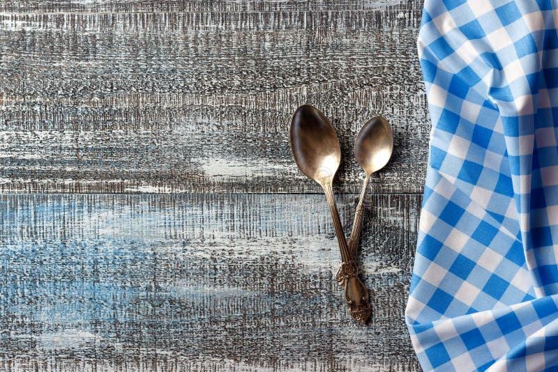 Trätabellbakgrund med bestick och den blåa rutiga vikta bordduken royaltyfri fotografi
