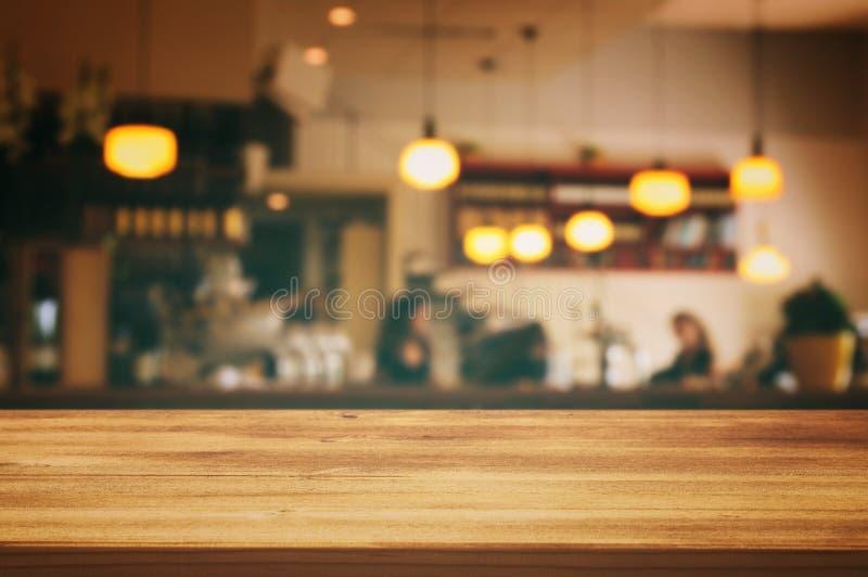trätabellen av den abstrakta suddiga restaurangen tänder framme bakgrund royaltyfri bild