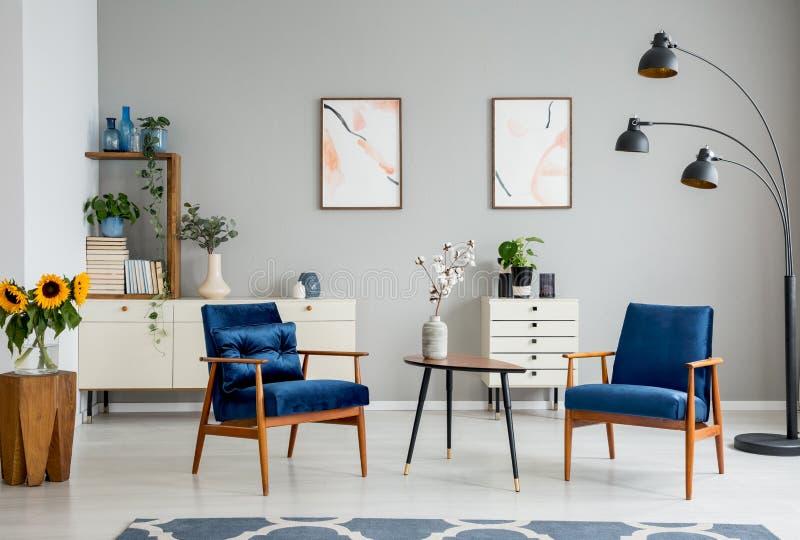 Trätabellen med blommor mellan blåa fåtöljer i grå färger sänker inre med affischer arkivbild