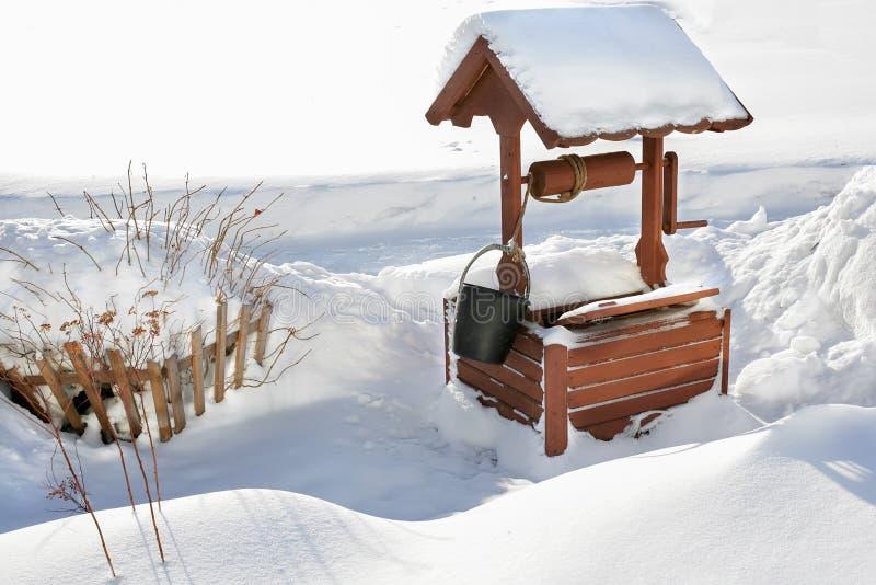 Trätappning väl med vatten i snön Vinterlandskap av den ryska baklandet En forntida apparat för royaltyfria foton
