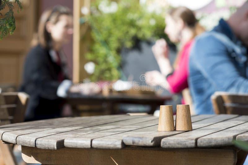 Trätappningnärbildtabell i kafét med besökare i bakgrunden Bakgrund arkivfoton