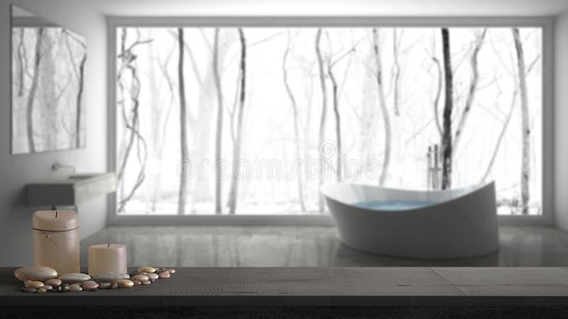 Trätappningtabellöverkant eller hylla med stearinljus och kiselstenar, zenlynne, över suddigt grått badrum med det stora panorama arkivfoto