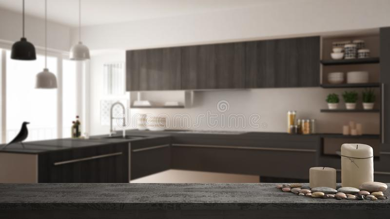 Trätappningtabellöverkant eller hylla med stearinljus och kiselstenar, zenlynne, över suddigt modernt minimalistic kök, grå arkit royaltyfria foton