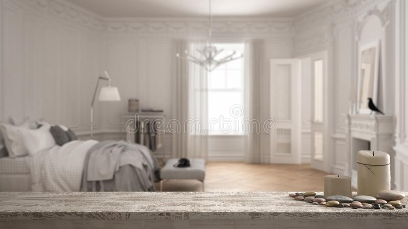Trätappningtabellöverkant eller hylla med stearinljus och kiselstenar, zenlynne, över suddigt tomt modernt scandinavian sovrum i  royaltyfri foto