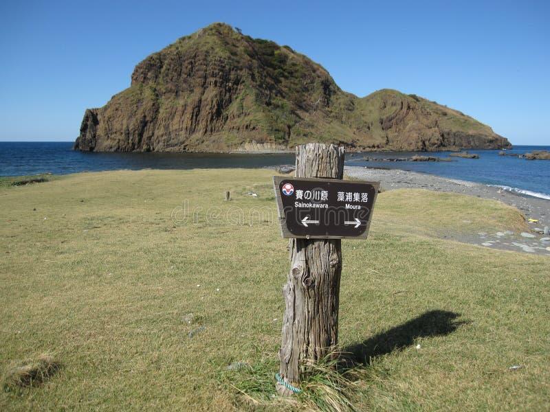 Trätecken som visar vägen på en japansk stenig kust royaltyfri foto