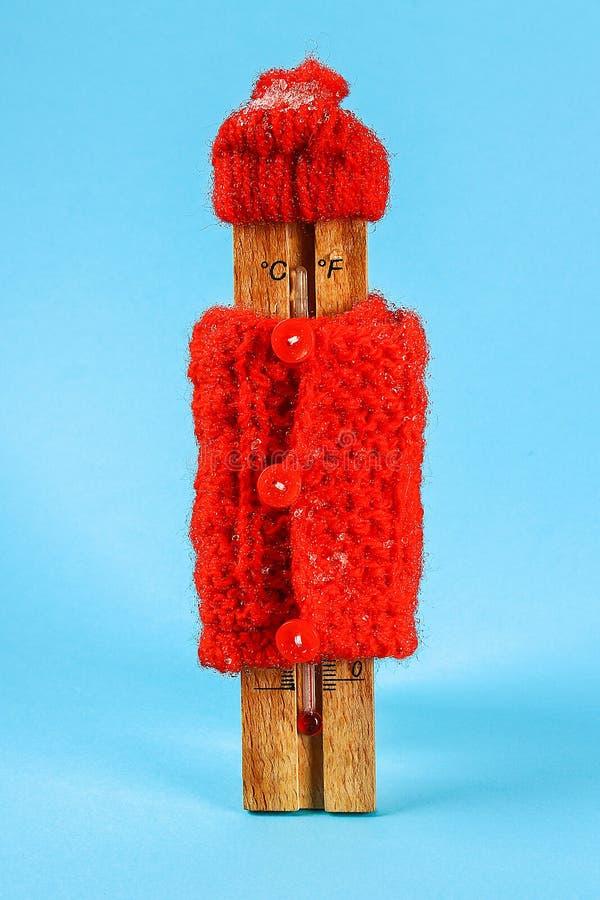 Trätermometer och att bära en röd hatt och tröja på en blå bakgrund royaltyfri fotografi